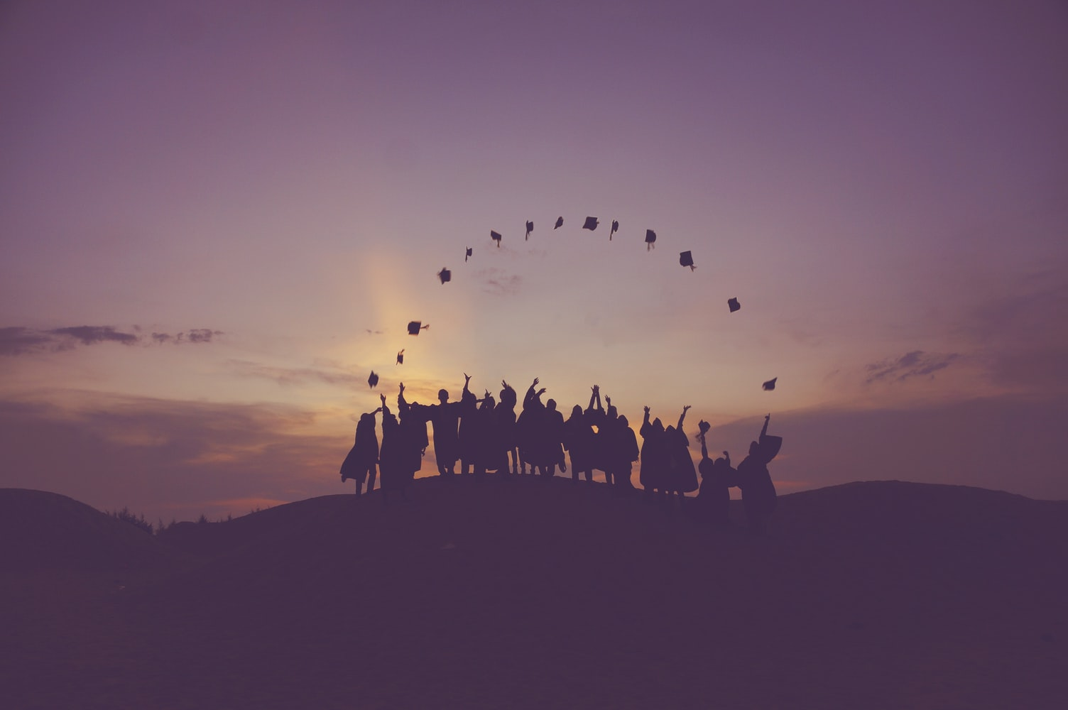 Graduates in nature with a darkening sky background, throwing caps into the air in a circle