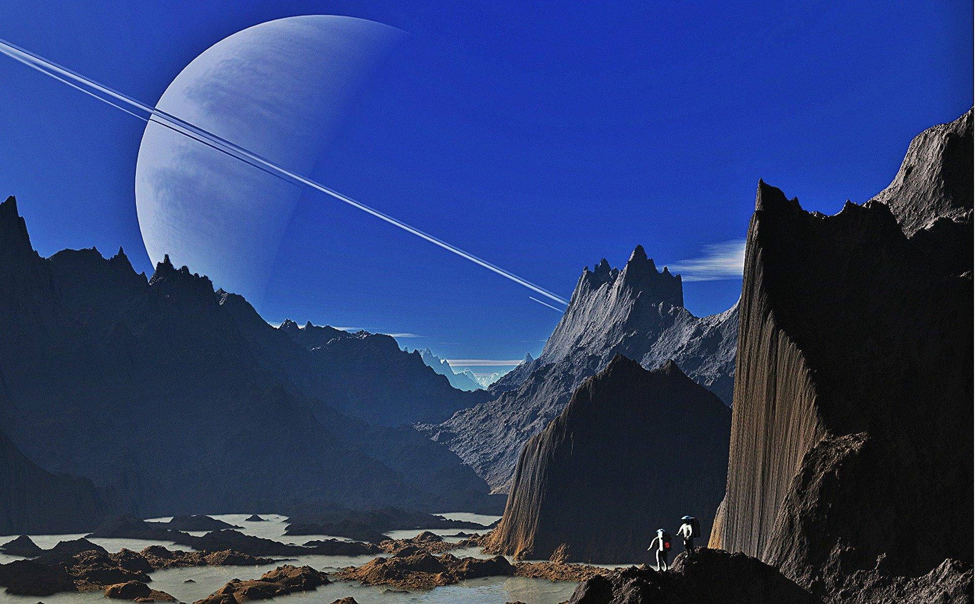 Image of two spacemen on rocky terrain, overlooking Saturn